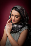 Attractive brunette woman in gray blouse and headscarf posing dramatic on purple background. Female art portrait, studio shot Stock Photo