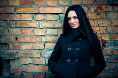 Attractive brunette woman with grunge wall Royalty Free Stock Image