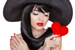 Attractive brunette woman with holiday makeup holding red heart Royalty Free Stock Images