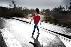Attractive black haired woman on the crosswalk royalty free stock photography