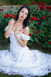 Attractive brunette woman in a long white dress, sitting in a bush blooming roses. Fashion, Wedding concept. royalty free stock photos