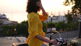 Attractive brunette woman in a long yellow dress enjoying the dawn standing by her city bicycle holding its handlebar