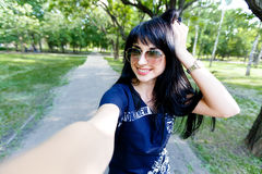 Attractive brunette woman makes selfie photos looking to camera Royalty Free Stock Image