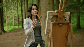 Attractive brunette woman painting a picture on canvas in a park. A tall slender girl is finishing work on her painting: landscape in the forest. Cloudy stock footage