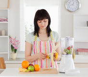 Attractive brunette woman pealing a banana. While standing in the kitchen Royalty Free Stock Photography