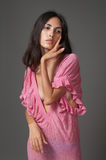 Attractive brunette woman in pink dress Stock Images