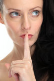 Attractive brunette woman placing the finger in front of her lips on white background Stock Images