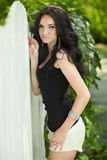 Attractive brunette woman posing near white fence at spring park Royalty Free Stock Images
