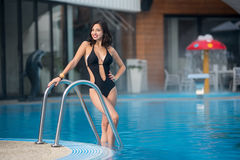 Attractive brunette woman is posing in the swimming pool in a black swimsuit on resort with blurred background Royalty Free Stock Images