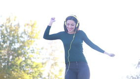 Attractive brunette woman putting on headphones and starts dancing stock footage