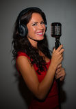 Attractive brunette woman recording a song. Royalty Free Stock Images