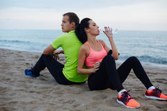 Attractive brunette woman refreshing with bottle of water exhausted after run. Young fit couple having break after workout outdoors, attractive brunette women Royalty Free Stock Photography