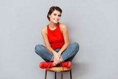 Attractive brunette woman sitting on the chair Stock Photography