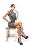 Attractive brunette woman sitting on stool Stock Images