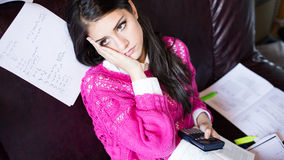 Attractive brunette woman student reading/ studying in her girly room Royalty Free Stock Photo