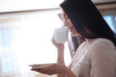 Attractive brunette woman taking a sip of coffee Stock Photography