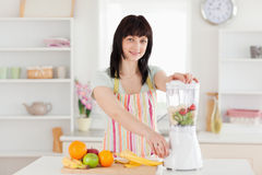 Attractive brunette woman using a blender Royalty Free Stock Photo