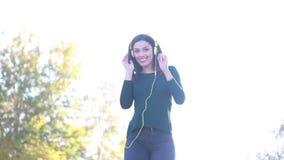 Attractive brunette woman wearing headphones and dancing stock video