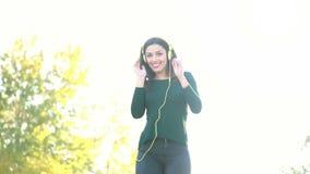 Attractive brunette woman wearing headphones and dancing stock video footage