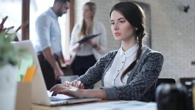 Attractive brunette women typing something in the laptop in light office. Other workers can be seen in the background stock footage