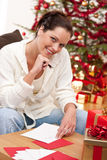 Attractive brunette writing Christmas cards Stock Photography