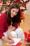 Attractive brunette writing Christmas cards Royalty Free Stock Photography