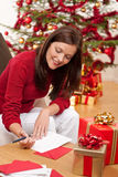 Attractive brunette writing Christmas cards Royalty Free Stock Image