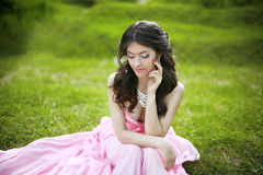 Attractive brunette young bride girl sitting on green grass at s Royalty Free Stock Photos