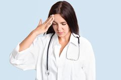 Attractive brunette young female nurse has headache after making diagnosis, keeps hand on forehead, concentrated down, dressed in royalty free stock photo
