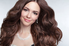 Attractive brunette young smiling woman Model Portrait. Long healthy Wavy hair. Professional makeup. Jewelry royalty free stock photos