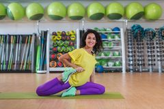 Attractive brunette young woman sitting on mat warming-up before training stretching her quadriceps in gym smiling and royalty free stock photography