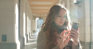 Attractive brunette young woman texting on phone in a city. stock photos