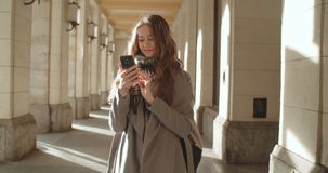 Attractive brunette young woman using phone in a city. Portrait of young smiling fashion girl standing with smartphone stock video