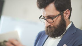 Attractive brutal man with a beard wearing a jacket uses mobile phone stock video footage