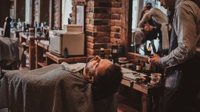 Thendy hairdresser at modern barbershop is working on client`s haircut. Attractive brutal men just got good beardcare from talanted trendy barber royalty free stock photography