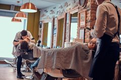 Thendy hairdresser at modern barbershop is working on client`s haircut. Attractive brutal men just got good beardcare from talanted trendy barber stock images