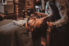 Thendy hairdresser at modern barbershop is working on client`s haircut. Attractive brutal men just got good beardcare from talanted trendy barber royalty free stock image
