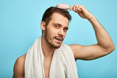 Attractive brutal sexy man using a comb. royalty free stock photos