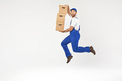 Attractive builder jumping with boxes Stock Photos