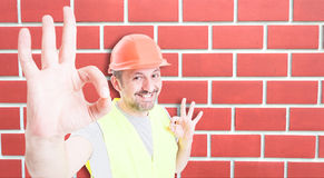 Attractive builder showing okay sign with happiness. Attractive builder showing double okay sign with happiness on brick wall background with text space Royalty Free Stock Photo