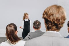 Attractive business coach gesturing and looking at participants at training. In hub stock photos