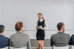 Attractive business coach holding documents during training. In hub stock image
