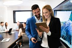 Attractive business couple using tablet in their company. Young attractive business couple using tablet in their company royalty free stock image