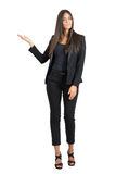 Attractive business fashion beauty in suit presenting with hands on copyspace Stock Photo