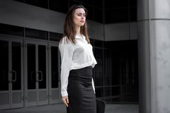 Attractive business girl stands on a street in a white shirt and black skirt Royalty Free Stock Images