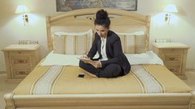 Attractive business lady talks on phone and uses digital tablet in a hotel room. Young businesswoman wearing black suit and with red lips sits on the bed in a stock video