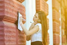 Attractive business lady talks on the phone and writes important information on paper. The working process. Portrait of a young brunette woman in a bright royalty free stock photos