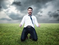 Attractive business man celebrates his victory. With dramatic sky stock photography