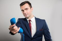 Attractive business man handing blue telephone receiver. On gray background with copyspace advertising area Royalty Free Stock Photo