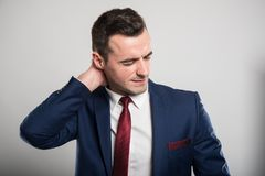 Attractive business man holding back neck like hurting. On gray background Royalty Free Stock Photo